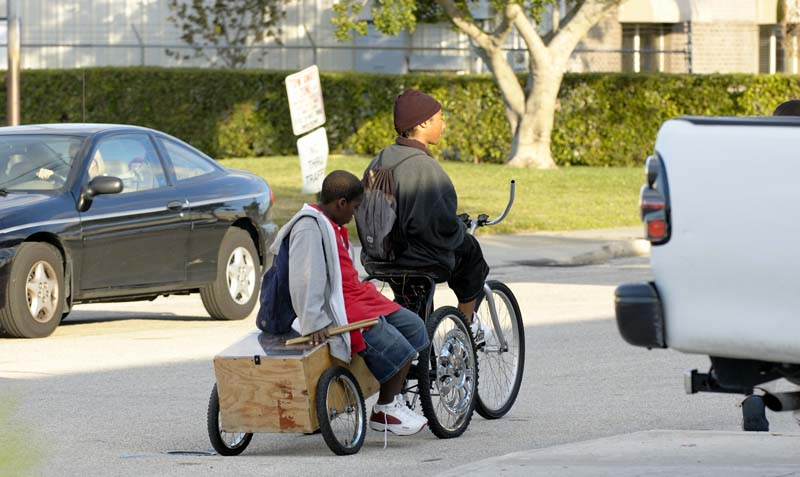 Carven\'s friend catches a ride to school on the back of his bike.