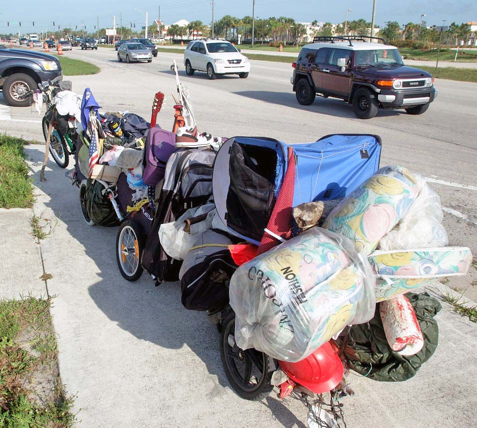 Bicycle with triple trailer being passed by a 2008 Toyota FJ Cruiser.