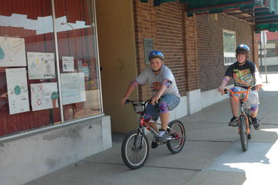 Adam Arnold, 14, of Fort Scott, demonstrates the proper use of bicycle safety equipment including the use of a helmet, elbow pads and knee pads while riding his bike Wednesday afternoon in downtown Fort Scott. Rayma Silvers/ Tribune Photo