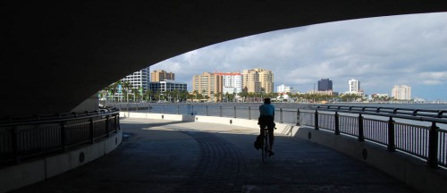 Jim Beloian rides north under the Royal Park Bridge toward West Palm Beach skyline