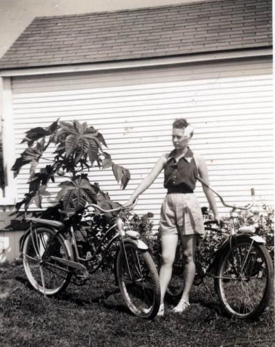 Mary Welch Steinhoff holds bikes in front of garage in Advance M