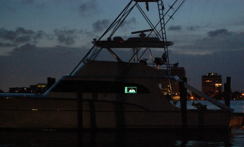 Palm Beach yacht with TV at dusk